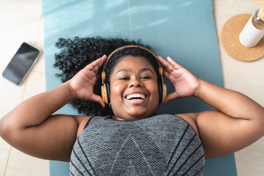 Happy curvy African woman having fun listening music with headphones while doing pilates at home