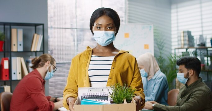 Portrait of young beautiful African American woman employee in medical mask standing in cabinet holding carton box with her goods, fired from work, lost job. Mixed-race workers behind at office, job