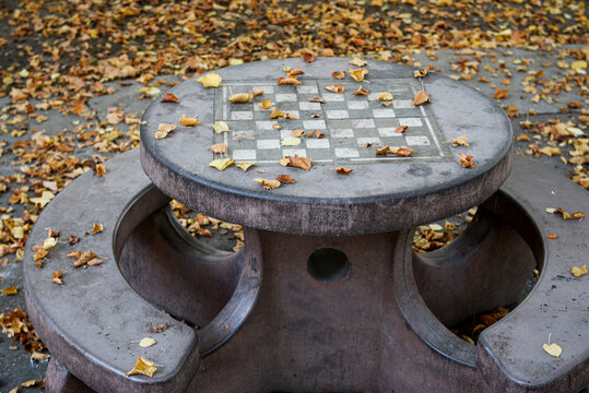 An empty chessboard on a concrete table outside in the Autumn, close-up, empty urban entertainment concept