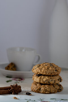 Oatmeal raisin cookies, spices and empty coffee cup against white background, comfort food concept