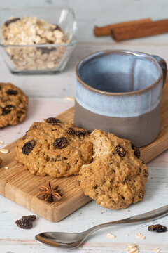 Oatmeal raisin cookies, spices and empty blue and grey cup, comfort food concept