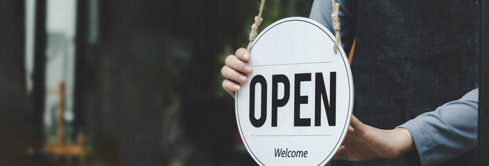 Fototapeta wide banner. Reopen. waitress hand turning open sign board on glass door in modern cafe coffee shop ready to service, cafe restaurant, retail store, small business owner, food and drink concept