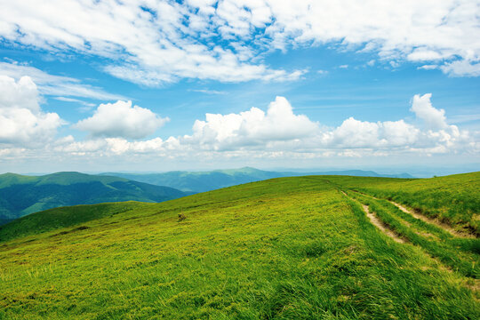country road through alpine meadow of carpathian mountain. beautiful nature landscape in summer. scenery with open view in to the distant ridge and valley. wonderful sky with clouds above the horizon