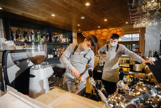 Two masked baristas prepare delicious coffee in the cafe bar. The work of restaurants and cafes during the pandemic.