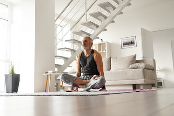 Strong older mid aged tattooed yogi man doing yoga exercises at home.Fit healthy mature senior tattooed male meditating relaxing lifting himself over mat sitting in yoga pose in living room at home.