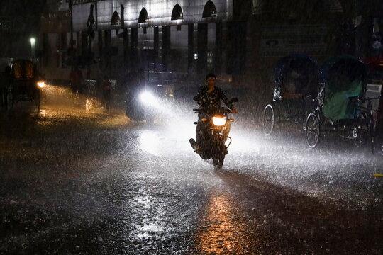 A man rides a bike during heavy rain at night in Dhaka