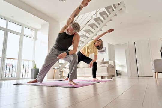 Fit middle aged 50s family couple doing fitness yoga morning exercise at home. Sporty healthy old mature man and woman training together standing in living room. Active seniors sport stretching.
