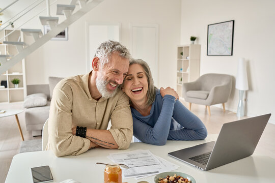 Happy mature older family couple laughing, bonding sitting at home table with laptop. Smiling middle aged senior 50s husband and wife having fun satisfied with buying insurance, paying bills online.