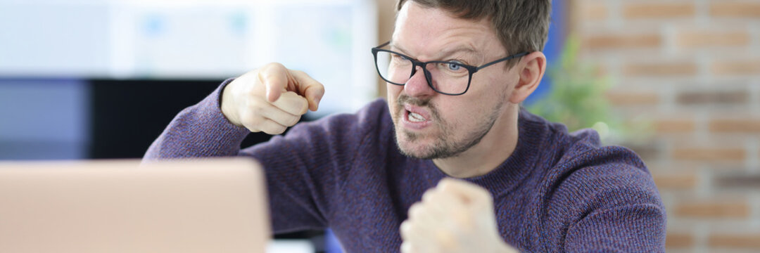 Angry man sits at work table in front of laptop