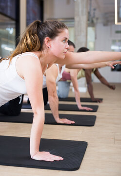 Portrait of young woman making pilates exercises with group in yoga studio