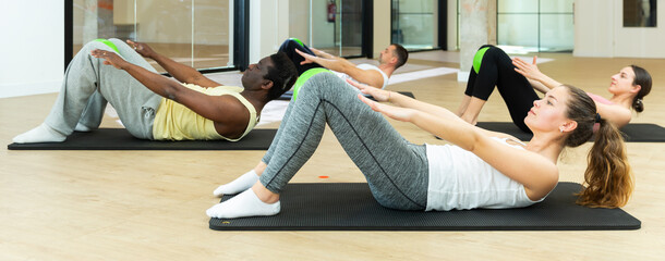 Young woman maintaining active lifestyle exercising with small pilates ball during group class in modern fitness center