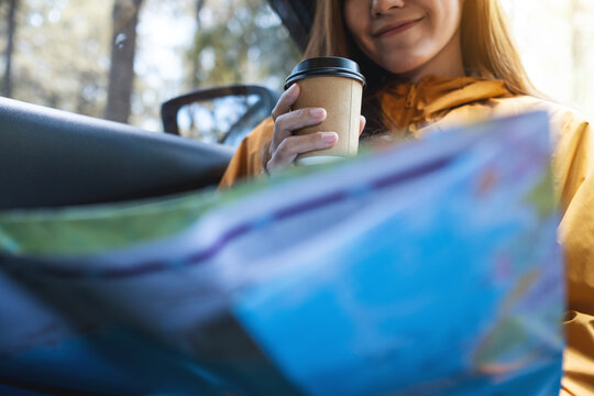 Closeup image of a young woman reading a map for direction and drinking coffee in the car