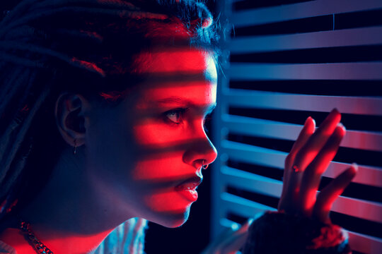 Portrait of a young woman in neon light, looking through the blinds. A trendy portrait with colored lighting and striped shadows.