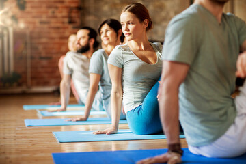 fitness, sport and healthy lifestyle concept - group of people doing yoga seated spinal twist pose in gym or studio