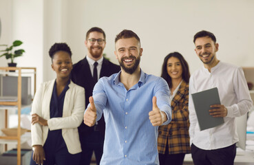 Obraz Happy smiling man team leader entrepreneur with thumbs up looking at camera standing together with group of multiracial millennial businesspeople on background. Teamwork, collaboration approval - fototapety do salonu