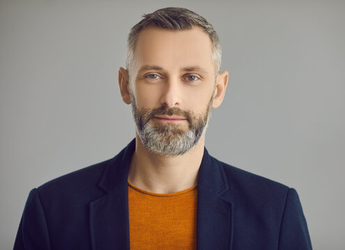 Handsome mature grey-haired caucasian hipster man with beard looking at camera face portrait on grey studio background. Masculinity, male beauty, style and fashion. Positive people emotion headshot