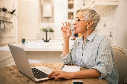 Indoor image of stylish mature woman digital marketing manager working remotely using laptop, developing advertising for online products, sitting at table, making notes, drinking water from glass