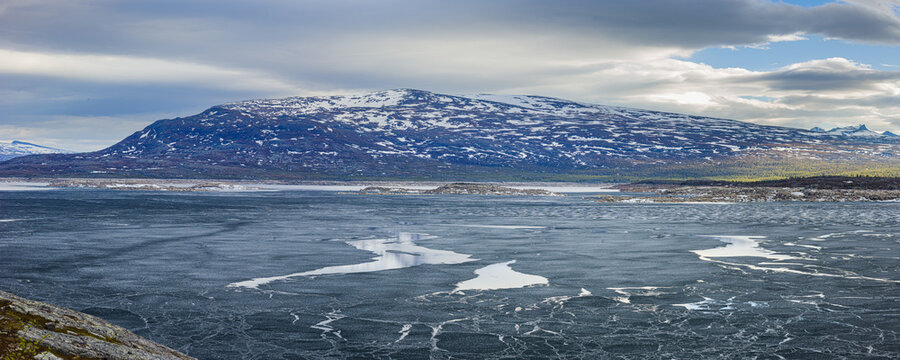 Panoramic image of a landscape in spring with the half frozen reservoir Akkajaure and mountains in Sarek National Park under overcast sky, Lapland, Sweden.