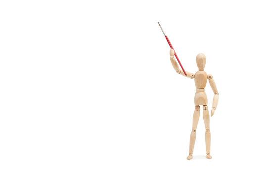Maniqui de madera sosteniendo un pincel con el brazo levantado sobre un fondo blanco liso y aislado. Vista de frente. Copy space