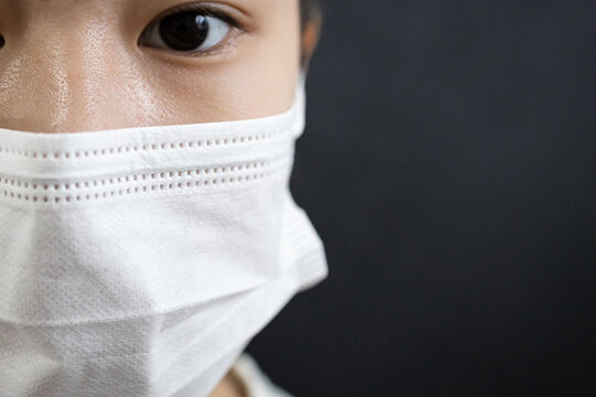Asian lady girl in a face mask,disease prevention campaign,wearing protective face masks before leaving home,in the city street,public,community,prevent contagious or spreading Coronavirus COVID-19