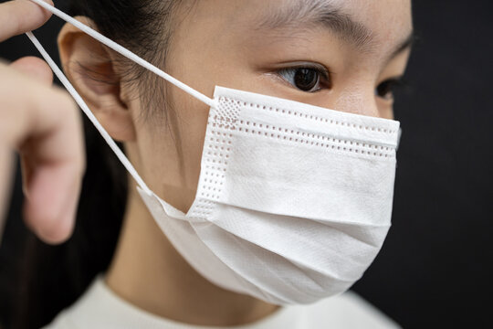 Asian child girl in a face mask,disease prevention campaign,wearing protective face masks before leaving home,in the city street,public,community,prevent contagious or spreading Coronavirus COVID-19