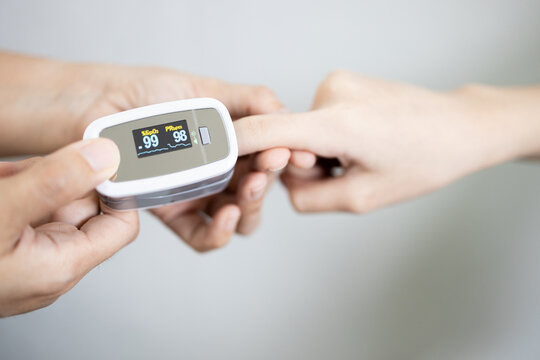 Fingertip pulse oximeter on the finger of young woman measuring heart rate (pulse) checking oxygen saturation (SpO2) level in the blood,diagnosis of Coronavirus or COVID-19 at home,health care concept