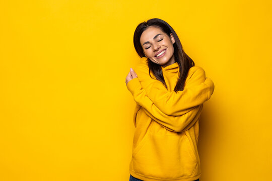 Young business woman hugs herself, smiling carefree and happy.
