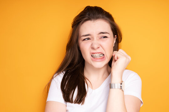 Girl in braces clenches her hand into a fist and frowns irritably with pain clenching her teeth
