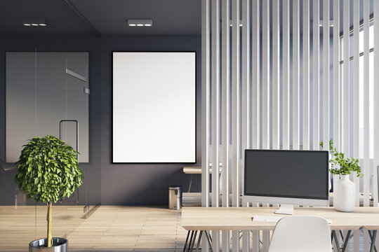 Blank white poster in black frame in stylish office room with eco wooden table with modern monitor and white wooden slatted partition behind. 3D rendering, mock up