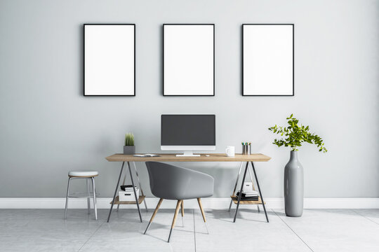 Blank white posters in black picture frame on light wall over stylish work place at home with monitor on wooden table, grey chair and vase on marble floor. 3D rendering, mock up