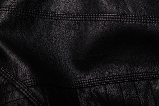 Black leather jacket texture with seams. Background or backdrop, clothing surface.