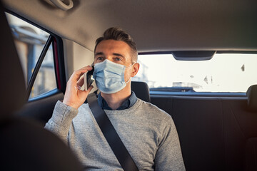Businessman sitting in a taxi while talking over phone with mask