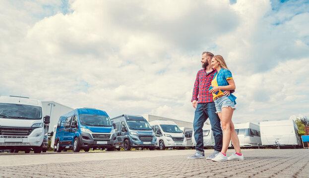 Woman and man choosing camper van to rent or buy