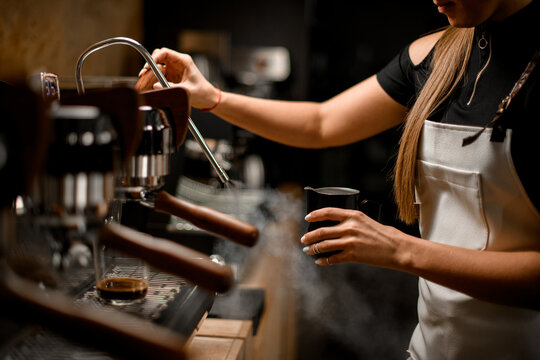 female barista turns on coffee machine that releases steam to make coffee drink