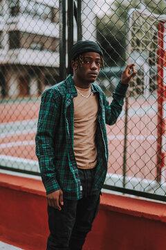 Chico negro joven y guapo posando junto a una cancha de baloncesto entre edificios