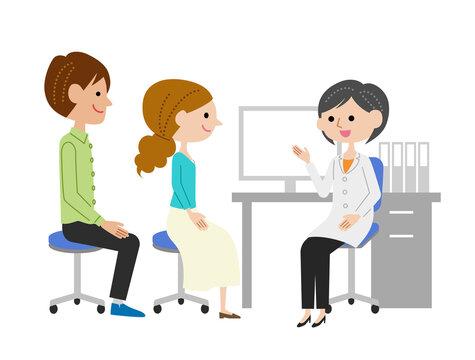 診察室で女医に説明を受ける若い夫婦
