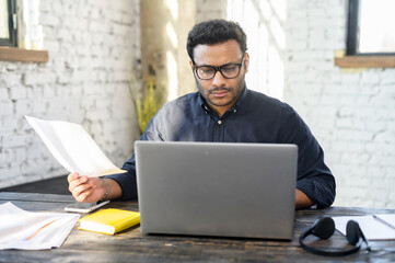 Fototapeta Executive mixed-race male office employee doing paperwork sitting at the desk with laptop in office, focused and serious hindu man in smart casual looking through sheets of documents, preparing report