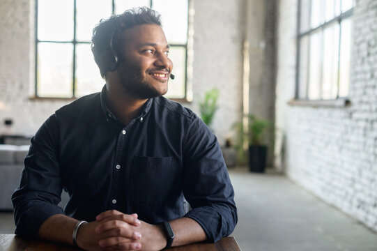 Delighted hindoo man wearing headset device and smart casual shirt looks away dreamily, support representative on the workplace in modern loft office, hindu guy in headphones with mic lost in thoughts