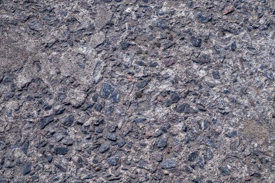 Background texture of an old concrete wall interspersed with black stones. Copy space