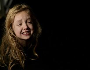 Obraz Horizontal, Close up portret of  crying young girl, on black background. - fototapety do salonu