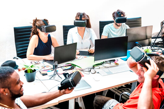 Young people employee workers having fun with vr virtual reality goggles in startup office - Human resource business concept at alternative studio coworking time - Start up entrepreneurs at work