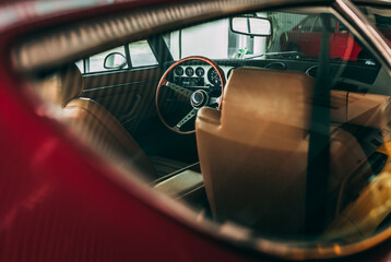 The interior of a retro car with leather seats, nardo steering wheel anddashboard