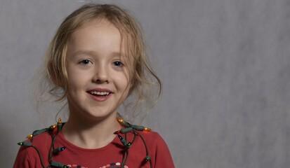 Śliczna dziewczynka w wieku przedszkolnym, w czerwonej bluzce, siedzi, jasne tło, portret horyzontalny.