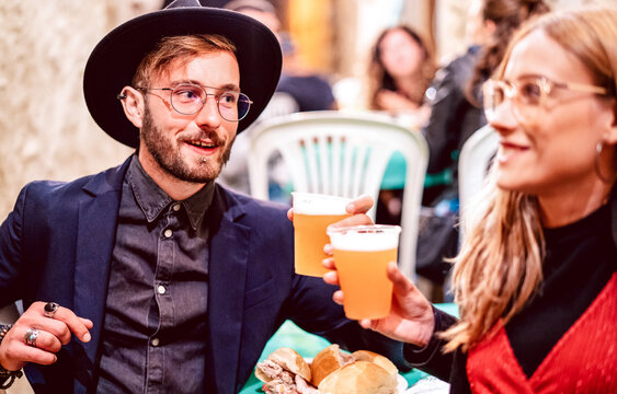 Young couple toasting beer glasses at street food festival - Beverage life style concept with friends having fun together on happy hour at brewery pub - Bright vivid filter with focus on guy with hat