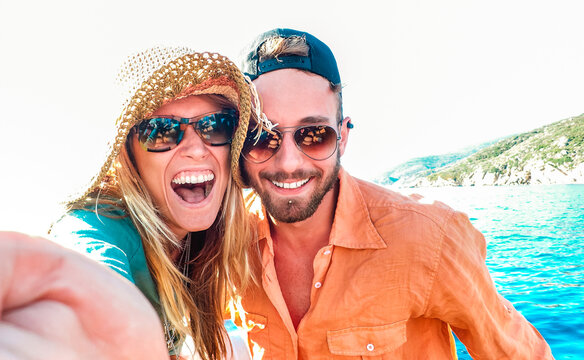 Young happy couple in love taking selfie at sailboat excursion with water camera - Boat trip life style in exotic scenarios - Youth lifestyle and travel concept around the world - Warm bright filter