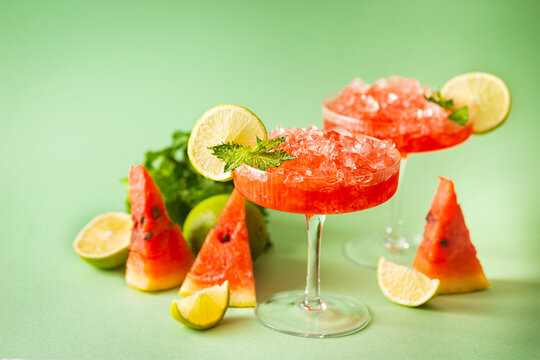 Watermelon frozen cocktail margarita with fresh watermelon, lime and mint on green background