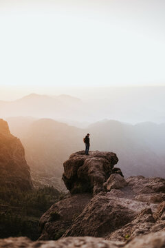 Man with a backpack standing on top of a cliff during the sunset