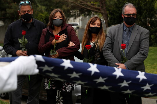 People wearing protective masks watch as the U.S. Naval funeral honors team fold the United States flag for Robert Cancemi, who served in the United States Navy, at a cemetery in the Brooklyn borough of New York City