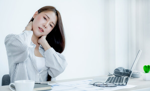 Young Asian businesswoman feeling pain and stretch herself after working hard on computer laptop for a long time, Office syndrome concept