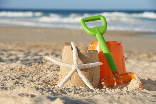 Bucket and spade next to starfish leanding against sandcastle at the beach